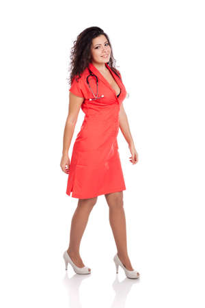 Sexy happy young nurse or medical woman doctor walking, wearing tangerine tango orange uniform dress , smiling. Full body isolated  on white background with text space. High resolution studio image. Stock Photo - 12631759