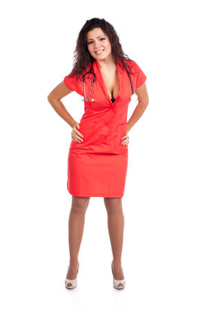 Attractive happy young nurse or medical woman doctor with big breasts, wearing tangerine tango orange uniform dress , smiling, hands on hips. Full body isolated on white background with text space. High resolution studio image. Stock Photo - 12631769