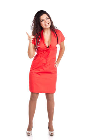 Sexy happy young nurse or medical woman doctor with big breasts, wearing tangerine tango orange uniform dress , smiling, and pointing attention with finger. Full body isolated  on white background with text space. High resolution studio image. Stock Photo - 12631770