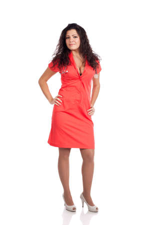 Beautiful professional young nurse or medical woman  doctor with big breasts, wearing tangerine tango orange uniform dress , holding hands on hips.  Full body isolated on white background with text space. High resolution studio image. Stock Photo - 12631763