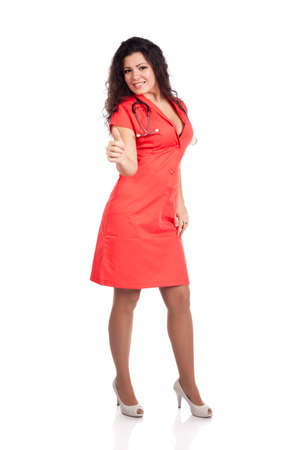 Attractive happy young nurse or medical woman doctor with big breasts, wearing tangerine tango orange uniform dress , smiling, with thumb up. Full body isolated  on white background with text space. High resolution studio image. photo