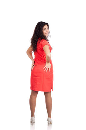 Back view of happy young nurse or medical woman doctor with big breasts, wearing tangerine tango orange uniform dress , smiling, hands on butt looking over shoulder. Full body isolated  on white background with text space. High resolution studio image. Stock Photo - 12631758