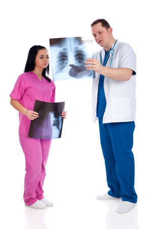Young couple of handsome man doctor and pretty nurse in blue and pink scrubs uniforms, analyzing a radiography of ribs and lungs. Full body image, isolated on white background. High resolution in studio, part of healthcare concept series. Stock Photo