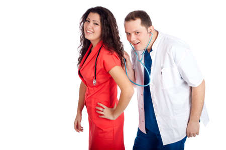 Couple of young doctors having fun, looking at camera. Man dressed in blue and white scrubs listens with stethoscope the nurse dressed in tangerine tango uniform. Healthcare concept series. photo