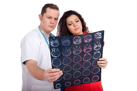 Young couple of handsome man doctor and pretty nurse in white and tangerine tango uniforms looking at a computed tomography scan (CT). High resolution image isolated on white background. Healthcare concept series. photo