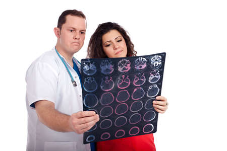 Confused couple of handsome man doctor and pretty nurse in white and tangerine tango uniforms looking at a computed tomography scan (CT). High resolution image isolated on white background. Healthcare concept series. photo
