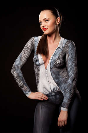 Artistic fashion concept of a businesswoman dressed in bodypaint office suit. Can be used for illustrating sexual issues at work. High resolution studio image on black background.