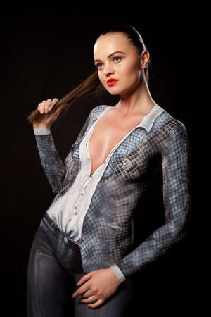 Artistic fashion concept of a businesswoman naked but covered in bodypaint office suit. Can be used for illustrating sexual issues at work. High resolution studio image on black background.