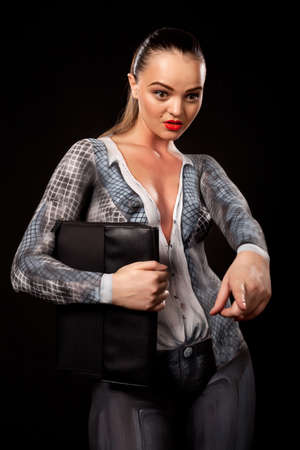 View of a sensual naked woman covered in body paint reperesenting office suit, holding a paper case and showing with her finger. High resolution concept image in studio on black background