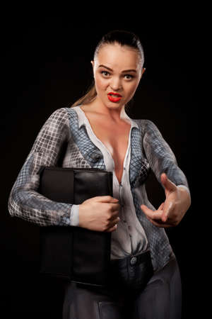 View of a sensual naked woman covered in body paint reperesenting office suit, holding a paper case and looking at camera. High resolution concept image in studio on black background Stock Photo