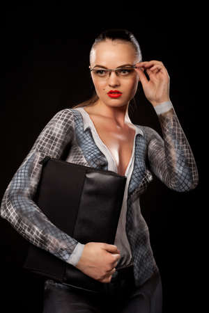 View of a sensual naked woman covered in body paint reperesenting office suit, wearing glasses and holding a paper case. High resolution concept image in studio on black background