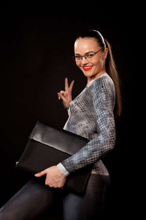 View of a sensual naked woman covered in body paint reperesenting office suit, wearing glasses and showing victory sign. High resolution concept image in studio on black background