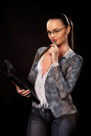 View of a sensual naked woman covered in body paint reperesenting office suit, wearing glasses and holding a paper case. High resolution concept image in studio on black background Stock Photo - 14177514