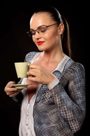 Happy sensual woman holding a green coffe or tea cup. She is naked, covered in business suit bodypainting. High resolution studio image on black background. Concept for sexual issues at work.