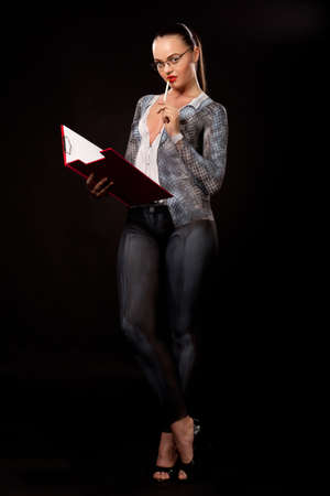 Full body view of a sensual naked woman covered in body paint reperesenting business suit, wearing glasses and holding a red paper case. High resolution concept image in studio on black background Stock Photo - 14176818