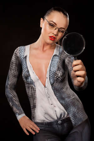 Naked shocked woman covered with body paint representing business suit, holding a magnyfing glass. Concept image of sexual issues at work. High resolution studio picture on black background.