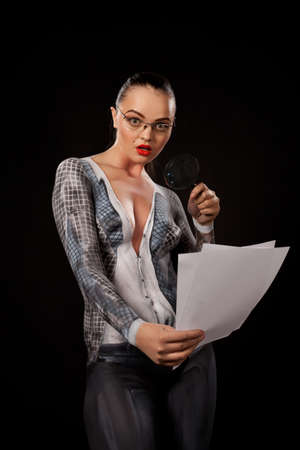 Naked shocked woman covered with body paint representing business suit, holding a magnyfing glass and blank documents. Concept image of sexual issues at work. High resolution studio picture on black background. Stock Photo - 14177093