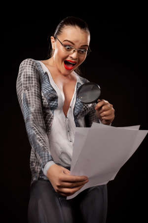 Naked shocked woman covered with body paint representing business suit, holding a magnyfing glass and blank documents. Concept image of sexual issues at work. High resolution studio picture on black background. Stock Photo