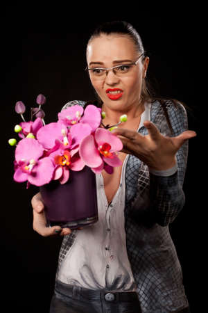 Dissapointed woman holding a purple flowers vase. She is naked, covered in business suit bodypainting. High resolution studio image on black background.