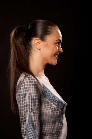 Profile of a happy attractive young executive woman that has checkered businessuit painted on naked body. Artistic bodypainting concept for sexual issues at work.