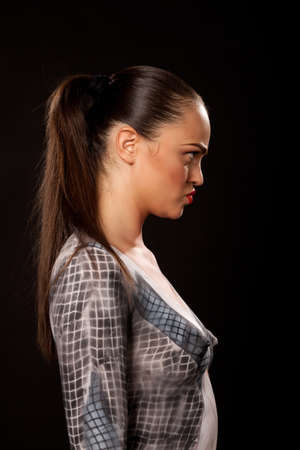 Profile of an angry attractive young executive woman that has checkered businessuit painted on naked body. Artistic bodypainting concept for sexual issues at work. Stock Photo