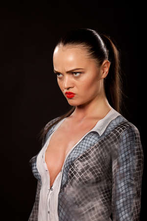Angry attractive young executive woman that has checkered businessuit painted on naked body. Artistic bodypainting concept for sexual issues at work.