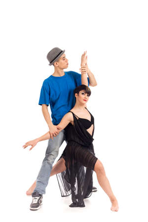 A couple of two young, attractive, modern ballet dancers, one woman and one man,  in dynamic action figure, on white background, studio image. Archivio Fotografico