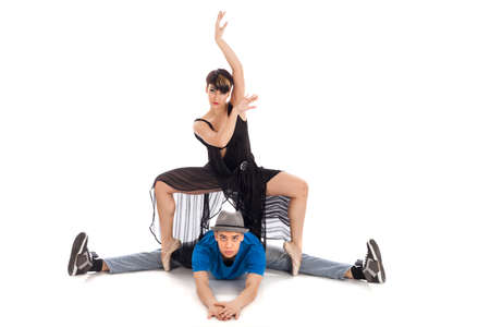 A couple of two young, attractive, modern ballet dancers, one woman and one man,  in dynamic action figure, on pointe, on white background, studio image.