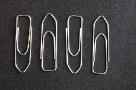 disorganized: metal paper clips on a black background