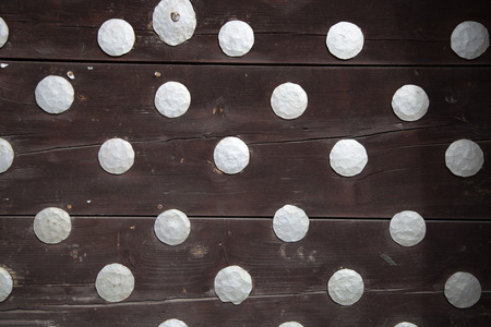 rivets: A black wooden boards with metal rivets Stock Photo