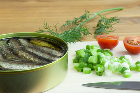 vegetable tin: sprats, onoin and tomatoes on a cutting board Stock Photo