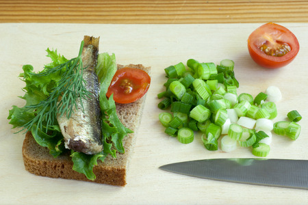 sardine can: sprats, onoin and tomatoes on a cutting board Stock Photo