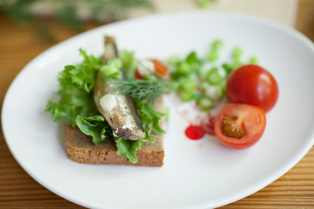sprats: sprats, bread and tomatoes on a saucer