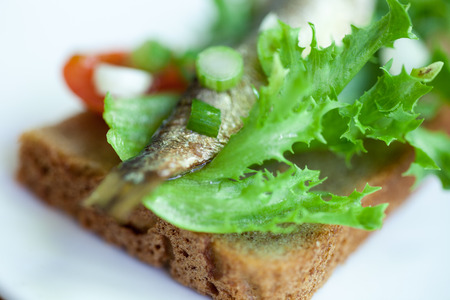 sardine can: partly blurred sprats on the bread closeup