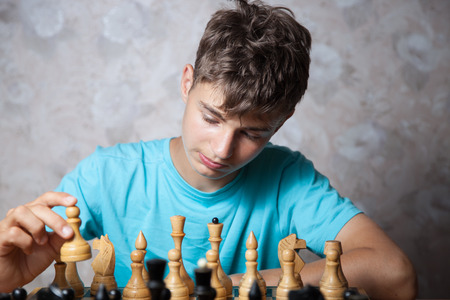sports backgrounds: Portrait of teenager playing chess Stock Photo