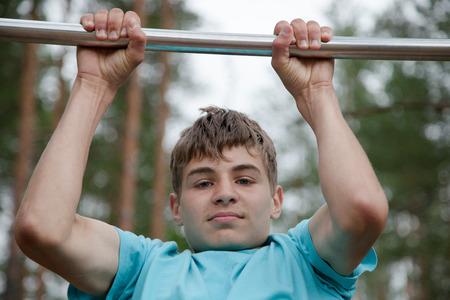 boy gymnast: The teenager doing exercise on a horizontal bar Stock Photo