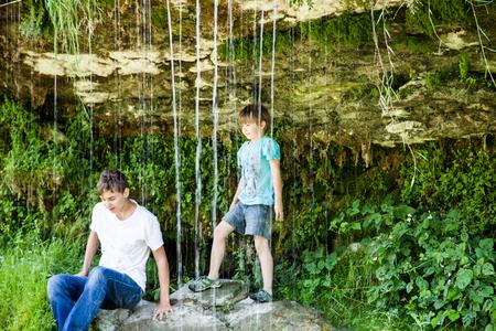 beautiful boys: Two brothers behind waterfall in Keila-Joa. Estonia