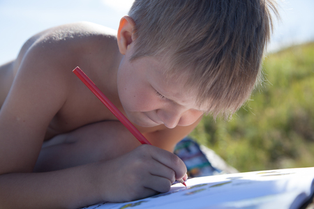 kids painted hands: The boy drawing a pencil