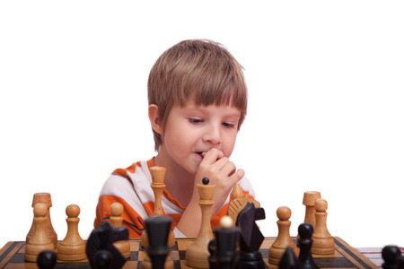 jugando ajedrez: poco lindo niño que juega al ajedrez