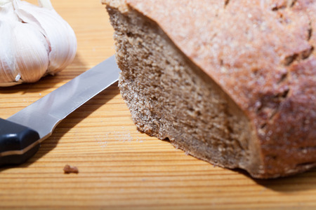 bread knife: Black bread, knife and garlic on the wooden table