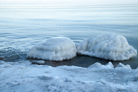 drifting ice: Stones covered with ice in the water