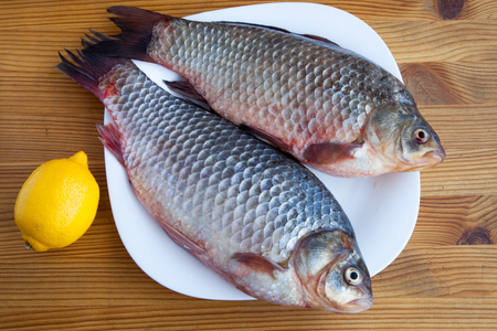 Fresh crucian fish on the wooden table Stock Photo