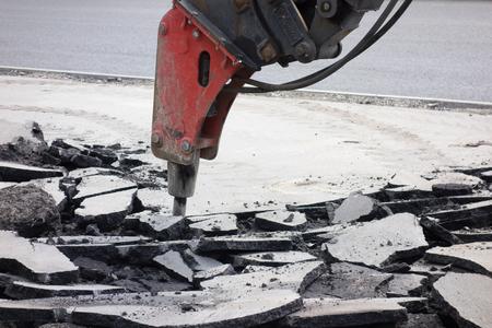 ストリート道路再建。ブルドーザー、油圧ブレーカー、古いアスファルトを分割します。