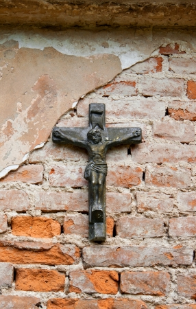 cross with a crucifixion on a brick wall photo