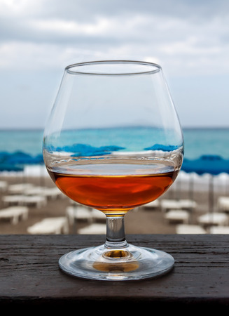 Wineglass of brandy on the background of the beach and sea photo