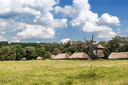 Rural landscape with a windmill and a wooden shed photo