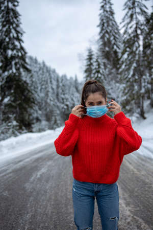 girl taking off protective neoprene face mask on the snowy road