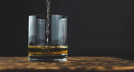glass of whiskey with ice on the wooden table, copy space