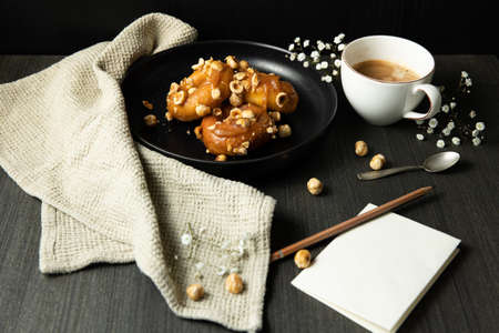 donuts with caramel and hazelnuts, cup of coffee on the rustic table, paper and pancil copy space