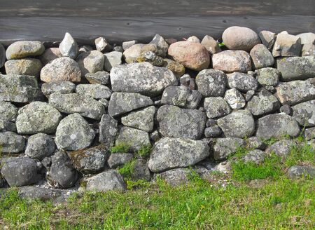 Ancient Foundation for a wooden house of large granite stones of different shapes and sizes. Banco de Imagens
